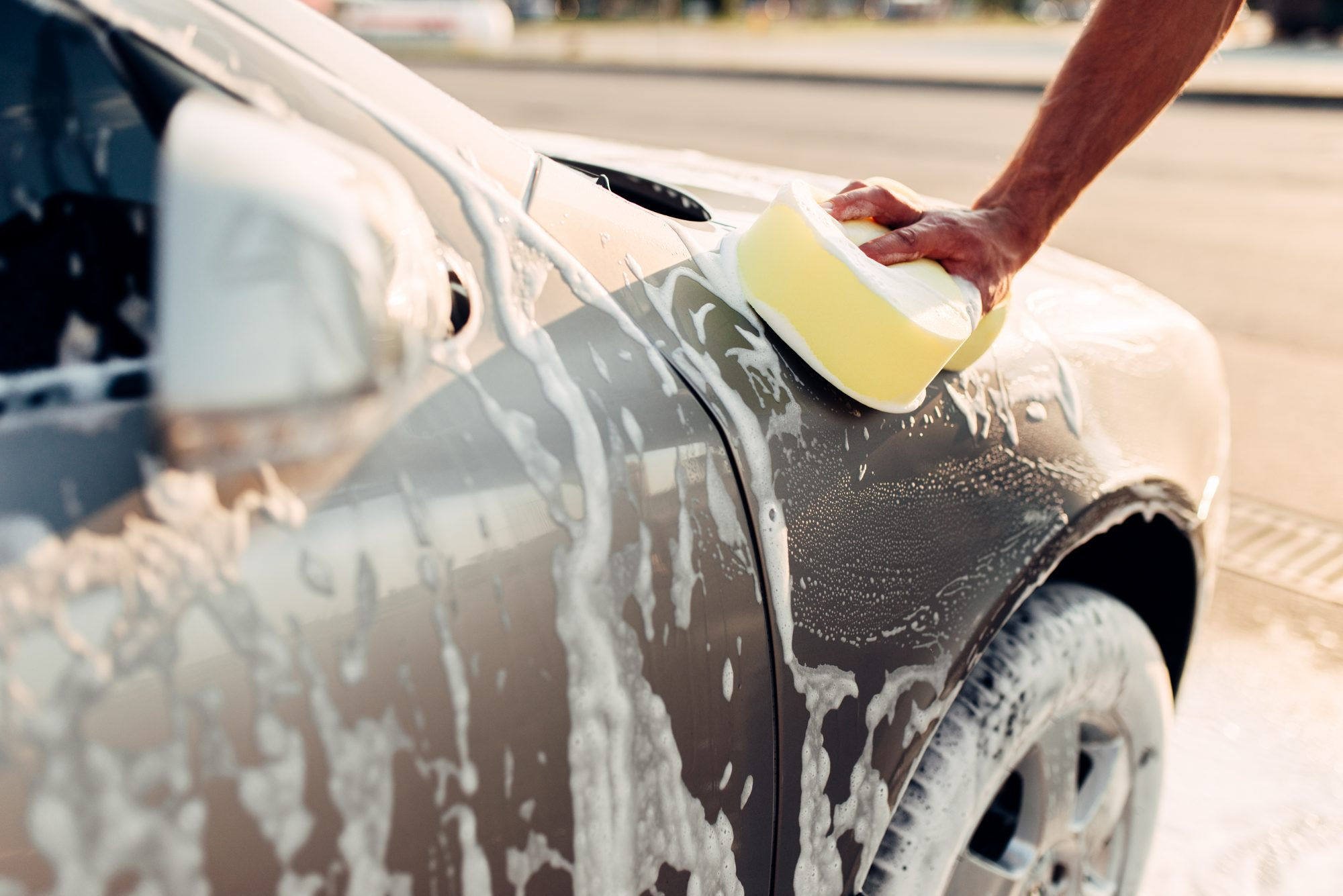 Male Hand Rubbing the Car with Soapy Foam